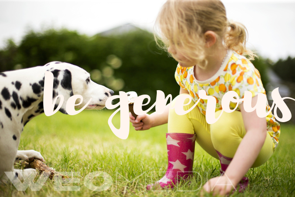 Little girl squatting down and sharing her ice cream cone with a dalmatian dog, with the words be generous layered over the top