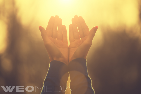 Hands held up in glowing sunlight to give thanks